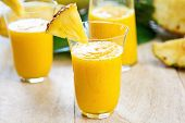 stock photo of jug  - Mango with pineapple smoothie in jug and glasses - JPG