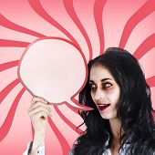 stock photo of psychodelic  - Psychodelic female zombie shouting out a halloween announcement through a blood red speech bubble - JPG