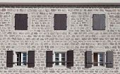 stock photo of jalousie  - Old stone building facade with dark brown windows and jalousies - JPG