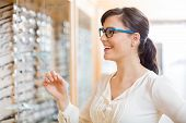 stock photo of spectacles  - Happy young woman trying new glasses at optician store - JPG