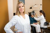 Portrait of mid adult female eye doctor with colleague examining patient in background