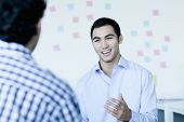 picture of button down shirt  - Two young businessman sitting and talking in office - JPG