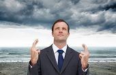 stock photo of fingers crossed  - Composite image of serious businessman with fingers crossed is looking up - JPG