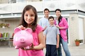 stock photo of coin bank  - Beautiful little girl inserting coin in a piggy bank with her family in background