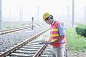 image of button down shirt  - Railroad worker in protective work wear checking the railroad tracks - JPG