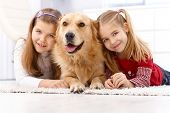 Happy little girls lying prone on floor at home with golden retriever, smiling.