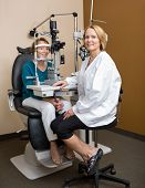 stock photo of slit  - Full length portrait of female optometrist examining senior patient - JPG