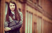 image of straight jacket  - Smiling confident young urban teenager with long straight brown hair standing outside a brick building in a trendy jacket looking at the camera with a friendly smile with copyspace - JPG