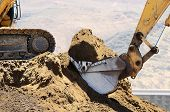stock photo of risen  - A large excavator works a dirt pile at a construction site - JPG