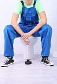 stock photo of plunger  - Plumber with toilet plunger on light background - JPG