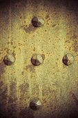 foto of stelles  - Brown grunge metal plate or armour texture with rivets as background - JPG
