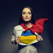 picture of independent woman  - Pretty woman opening her shirt painted in ukrainian flag colors like superhero - JPG