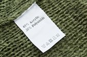 stock photo of khakis  - Knitted khaki cloth with composition and washing instructions label - JPG