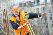 foto of theodolite  - One surveyor worker working with theodolite transit equipment at road construction site outdoors - JPG