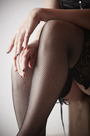 picture of fishnet stockings  - Beautiful voluptuous and sexy caucasian adult woman in black fishnet stockings and garters in a boudoir setting lit from the side with window light - JPG