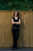 Smiling Young Woman Outdoors Leanign Against Wooden Fence poster