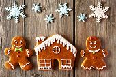 picture of gingerbread house  - Christmas homemade gingerbread couple and house on wooden table - JPG