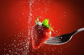 stock photo of vegetable food fruit  - Strawberry on a fork punctured falling sugar with red background detail - JPG