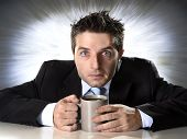 picture of addict  - young addict businessman in suit and tie holding cup of coffee anxious and crazy in caffeine addiction and need to keep awaken on zoom effect grunge background - JPG