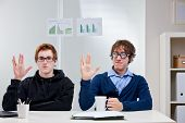 picture of dorky  - Two young office workers in a nerd attitude showing a typical science fiction greeting in a funny way - JPG