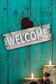 stock photo of log fence  - Wood welcome sign with country heart by burning log candles hanging on antique green door - JPG