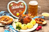 foto of pretzels  - Appetizing Bavarian roast pork knuckle with dumplings and pretzel - JPG