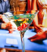 stock photo of roulette table  - red dice in the cocktail glass in front of gambling table casino concept - JPG
