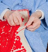 picture of welts  - Old woman sitting on the bed and sewing - JPG