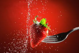 pic of sweet food  - Strawberry on a fork punctured falling sugar with red background detail - JPG