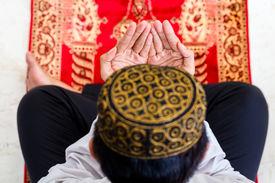 pic of muslim man  - Asian Muslim man praying on carpet wearing traditional dress - JPG