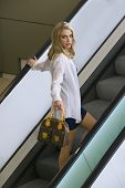 picture of short skirt  - Portrait in color of a sexy blonde woman wearing a short black skirt and white shirt ascending an escalator in an urban setting, looking back over her shoulder and holding a handbag