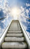 foto of escalator  - The escalator is moving up to the blue sky with the luminous Sun - JPG