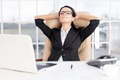 stock photo of human eye  - Cheerful young business woman holding head in hands and keeping eyes closed while sitting at her working place - JPG