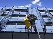 foto of window washing  - Climber wash windows and glass facade of the skyscraper - JPG
