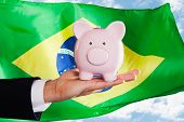 picture of brazilian money  - Businessman Holding Piggybank In Front Of Brazilian Flag - JPG