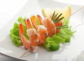 stock photo of leek  - Roasted shrimps on the skewer with fresh green lettuce leek rosemary and lemon on the white plate - JPG