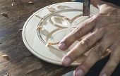 stock photo of woodcarving  - Woodcarver makes threaded plate - JPG