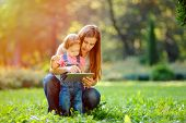 stock photo of happy day  - Beautiful mother and kid girl playing at tablet pc outdoors in fall - JPG