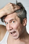 foto of alopecia  - Man with mirror looking at his hair on gray background - JPG