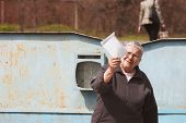 image of postman  - Mature woman shows letter from postman - JPG