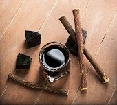 stock photo of licorice  - Licorice liqueur with pure blocks and roots on wooden table - JPG