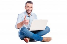 stock photo of denim wear  - Handsome young man in casual wear sitting on the floor with laptop and showing his thumb up while being isolated on white background - JPG