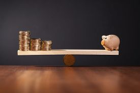 foto of seesaw  - Seesaw with piggy bank on one side and stack of money on the other side - JPG