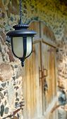 pic of stone house  - Nice lantern hanging on the wall of stone house - JPG
