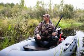 pic of hunter  - Hunter sitting in a motor boat on the river - JPG