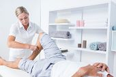 stock photo of calves  - Physiotherapist doing calf massage to her patient in medical office - JPG
