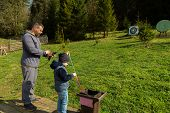 image of shoot out  - Father and son shoot arrows at a target - JPG