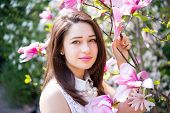 stock photo of magnolia  - beautiful smiling girl holding a branch of magnolia - JPG