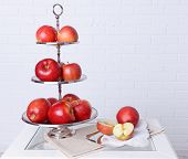 picture of serving tray  - Tasty ripe apples on serving tray on brick wall background - JPG