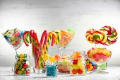 stock photo of jar jelly  - Colorful candies in jars on table on wooden background - JPG